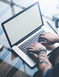 Young tattooed coworker working on laptop with white empty computer screen at sunny office.Businessman typing on. Notebook keyboard.Vertical mockup,blurred royalty free stock image