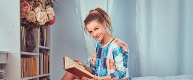 A beauty tattoed girl in casual clothes. Young tattooed girl read a book sitting on a sofa at home royalty free stock images