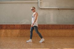 Young tattooed hipster man with sunglasses walking Royalty Free Stock Images