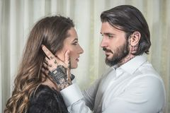 Young tattooed man holding for kiss a blonde woman. Young tattooed men holding for kiss a blonde women in doors Stock Photos