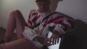 Young tattooed man lying on floor with working static tv, touching screen. Young stylish tattooed caucasian man in cap, sportive jacket and pink pants lying on stock video