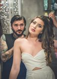 Young tattooed man reaching to a sensual woman looking in the mi. Young tattooed men reaching to a sensual women looking in the mirror, in the bathroom Royalty Free Stock Photos
