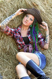 Young tattooed stylish woman with dreadlocks in cowgirl style. On haystack background stock image