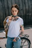 Young tattooed woman with closed eyes holding jacket over shoulder. Near bicycle stock photography