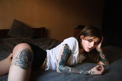Young tattooed woman laying in bed. Wearing white t-short and black shorts Stock Images