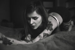 Young tattooed woman with long hair poses in the bed Royalty Free Stock Photos