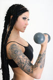 Young tattooed woman with old dumbbells Royalty Free Stock Photo
