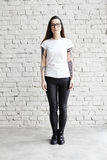 Young tattooed woman wearing blank t-shirt, standing in front of brick wall in loft. Royalty Free Stock Photography