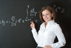 Young teacher. Is standing near blackboard in classroom stock photography
