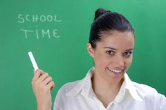 Young teacher. Young beautiful teacher in white on green background stock images