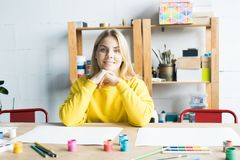 Young teacher at art class. Portrait of smiling young woman sitting at the table in art class and waiting for her pupils royalty free stock photo