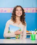 Young Teacher With Book Sitting At Desk Royalty Free Stock Image
