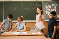 Young teacher check childrens work. Schoolboy and schoolgirl study.  royalty free stock photography