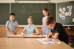 Young teacher check childrens work. Schoolboy and schoolgirl study.  stock image