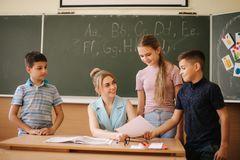 Young teacher check childrens work. Schoolboy and schoolgirl study.  royalty free stock image