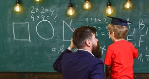 Young teacher explaining arithmetic to the little boy in academic cap. Man with beard and blond child turned back in the. Classroom. Guy pointing at the board Royalty Free Stock Image