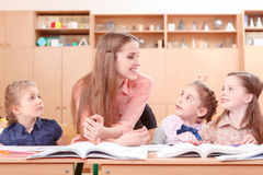 Young teacher explaining material to pupils Royalty Free Stock Photo
