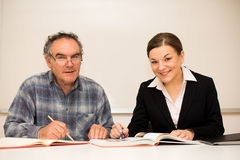 Young teacher explaining somethng to eldery man. Intergeneration Royalty Free Stock Images