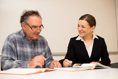 Young teacher explaining somethng to eldery man. Intergeneration. Al transfer of knowledge Stock Photo