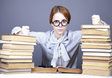 The young teacher in glasses with books.