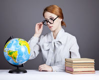 The young teacher in glasses with books and globe Royalty Free Stock Photography