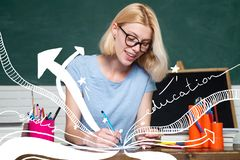 Young teacher in glasses over green chalkboard background. Portrait of creative young smiling female Student in glasses stock image