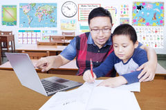 Young teacher guides his student to learn. Portrait of young male teacher helps his student to study with laptop in the classroom Royalty Free Stock Photography
