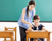 Young Teacher helping child with writing lesson Royalty Free Stock Photo