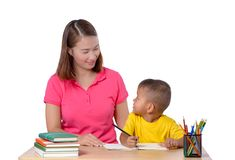 Young Teacher helping child with writing lesson isolated on whit stock images