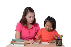 Young Teacher helping child with writing lesson isolated on white background royalty free stock images