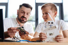 Young teacher helping his student with robot construction Royalty Free Stock Photo