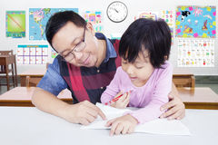 Young teacher helps student to write Royalty Free Stock Photography