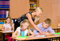 Young teacher helps students of primary school in the exam Royalty Free Stock Photos