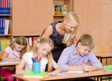 Young teacher helps students of primary school in the exam.  Royalty Free Stock Image