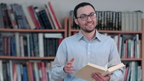 Young teacher holding book and looking at the camera. Close up. Professional shot in 4K resolution. 075. You can use it e.g. in your commercial video, business stock footage