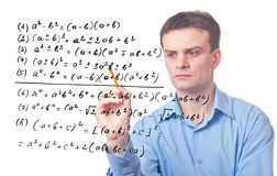 Young teacher and Mathematical formula. Young teacher drawing a Mathematical formula. Isolated Stock Image