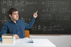Young teacher is pointing on math formulas on blackboard with finger.  stock photos