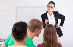 Young teacher pointing on talking student Royalty Free Stock Images