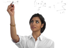 Young teacher presenting equations. Young, beautiful teacher/businesswoman presenting/solving equations on a see-through screen Stock Photography