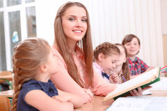 Young teacher reading to pupils Royalty Free Stock Image