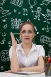 Young teacher is sitting near blackboard in classroom