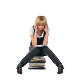 A young teacher is sitting on a sack of books Stock Images