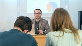 Young teacher sitting in school classroom with laptop, talking to students. Professional shot in 4K resolution. 075. You can use it e.g. in your commercial Royalty Free Stock Images