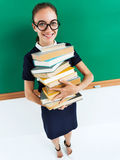 Young teacher with stack of books near blackboard Royalty Free Stock Image