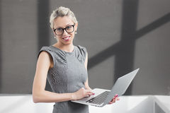 Young teacher standing in front af blackboard with laptop computer Royalty Free Stock Photography