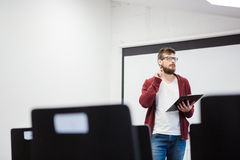 Young teacher standing near the whiteboard in classroom Royalty Free Stock Image