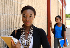 A young teacher with a student in the background. A young African teacher posed next to a wall with a student in the background out of focus Stock Images