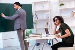 The young teacher and student in the classroom. Young teacher and student in the classroom stock photography