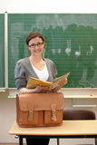 Young teacher or student in the classroom. Or university is smiling with book and bag Royalty Free Stock Image