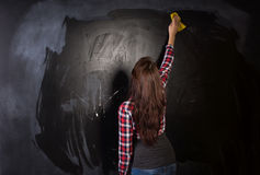 Young teacher or student cleaning the blackboard Royalty Free Stock Photography